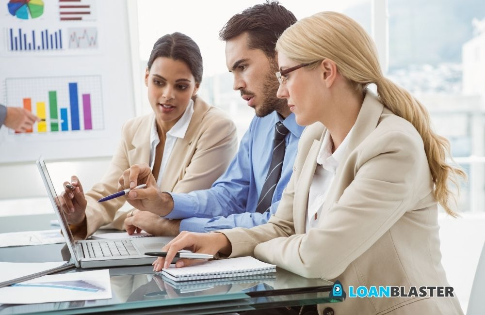 business people discussing in front of a laptop